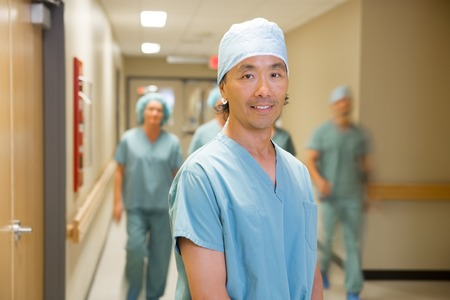 Portrait of male doctor with medical team walking in background at hospital corridor photo