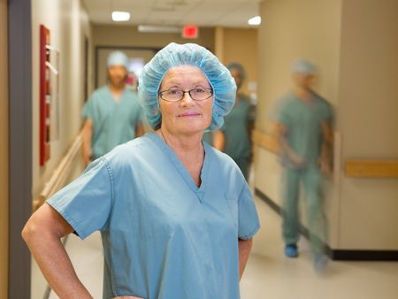 Portrait of confident female doctor with team walking in hospital corridor photo