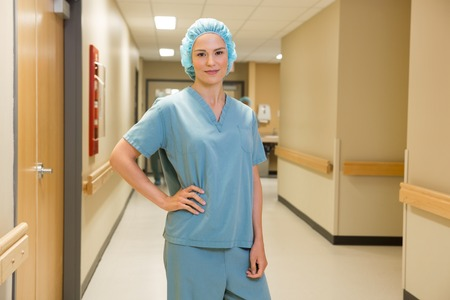 enfermera con cofia: Retrato del doctor de sexo femenino confidente con la mano en la cadera de pie en el pasillo del hospital