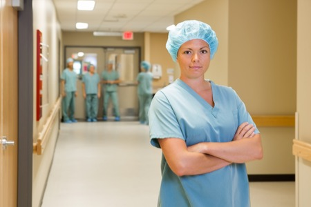 Portrait of female doctor standing arms crossed with team in background at hospital corridor photo