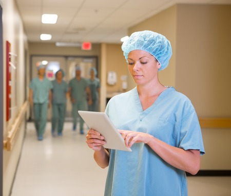 Female doctor using digital tablet in hospital corridor photo