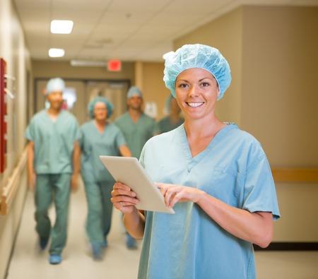 enfermera con cofia: Retrato de la feliz mujer médico con la tableta digital mientras las personas que recorren en pasillo del hospital