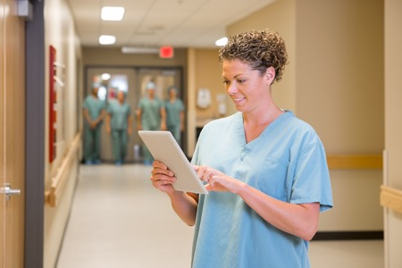 Young female doctor using digital tablet with team standing in background at hospital corridor photo