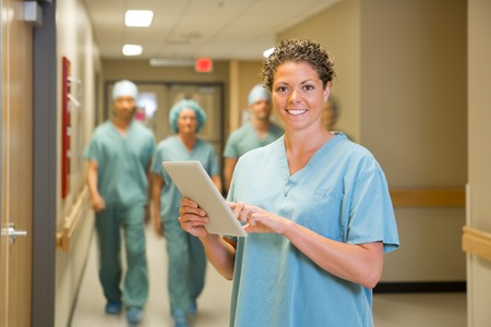 health professionals: Portrait of happy female surgeon holding digital tablet with team walking in hospital corridor