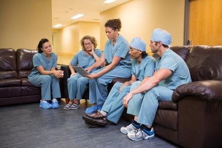 医師や看護師が病院の待合室でデジタル タブレットを使用しての完全な長さ