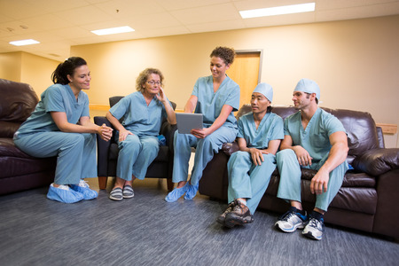 waiting area: Surgical team in staff lounge looking at digital tablet