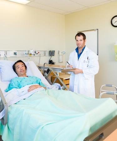paciente en camilla: Retrato de médico escrito en el portapapeles, mientras que de pie junto a la cama del paciente en el hospital Foto de archivo