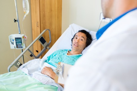 Mature male patient looking at doctor while lying on bed in hospital photo