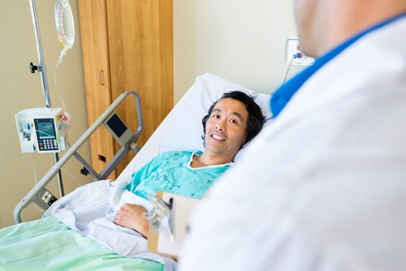 inpatient: Happy mature male patient looking at doctor while lying on bed in hospital Stock Photo