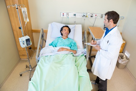 High angle view of young male doctor looking at patient while writing notes on clipboard in hospital room photo
