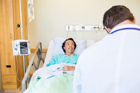 paciente en camilla: Sonriendo paciente de sexo masculino que mira al doctor mientras está acostado en la cama en la habitación del hospital