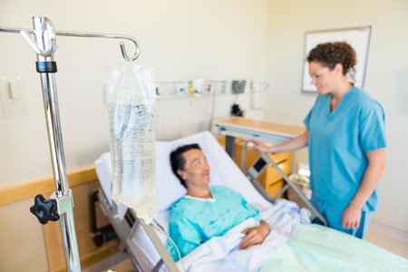 Closeup of IV bag with nurse and patient looking at each other in background at hospital Stock Photo