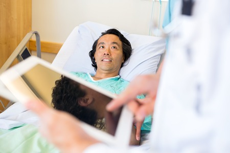 Mature male patient looking at doctor using digital tablet in hospital photo