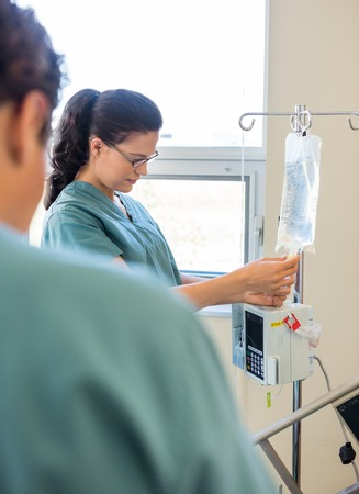 Young nurse adjusting IV bag with coworker in foreground in hospital photo