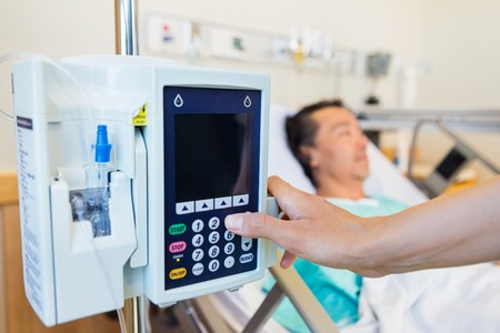 iv: Closeup of nurses hand operating IV machine while patient lying on bed in hospital Stock Photo