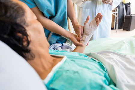 Midsection of nurse putting bandage on patient's hand while standing by doctor at hospital photo