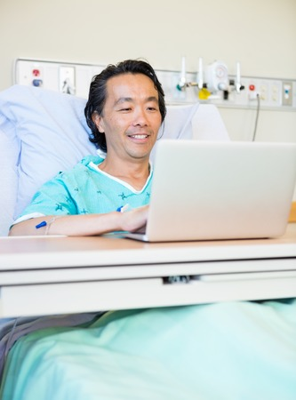 inpatient: Happy mature male patient using laptop on bed in hospital