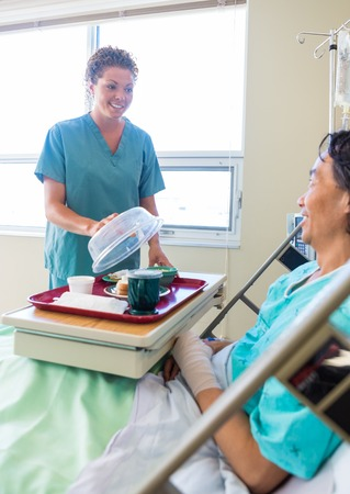 Mid adult nurse lifting cover from food plate for male patient in hospital Stock Photo