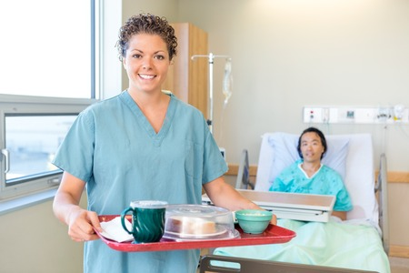 Portrait of happy mid adult nurse holding breakfast tray with patient lying on bed in background at hospital Stock Photo