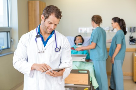 inpatient: Male doctor using digital tablet while nurses serving breakfast to patient in hospital Stock Photo