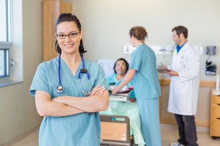 Portrait of confident nurse with arms crossed standing against patient and medical team at hospital