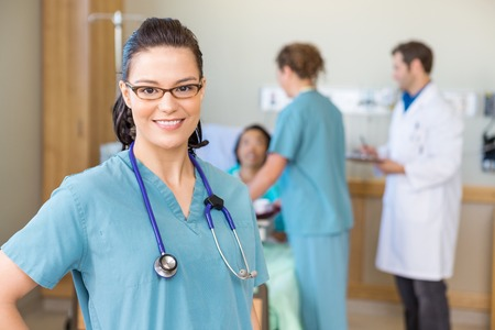 enfermera: Retrato de la enfermera sonriente confianza contra el paciente y el equipo médico en el hospital