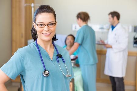 Ritratto di infermiera fiducioso sorridente contro pazienti e personale medico in ospedale
