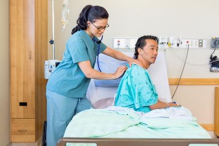 Enfermera joven que examina la espalda del paciente de sexo masculino con el estetoscopio en la cama en el hospital Foto de archivo