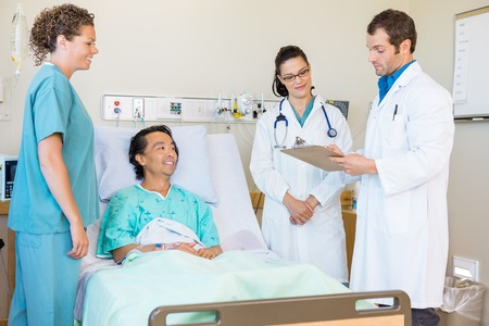 Young doctors discussing notes while nurse and patient looking at them in hospital room photo