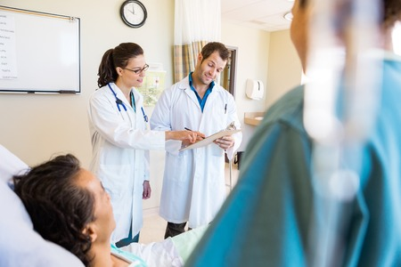 Young doctors discussing notes with patient and nurse in foreground at hospital room photo