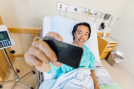 Mature male patient taking self portrait through cell phone in hospital photo