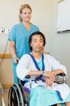 Portrait of mature male patient sitting on wheelchair while nurse assisting him in hospital photo