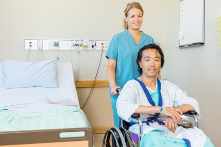 Portrait of mature patient sitting on wheelchair while nurse assisting him in hospital photo