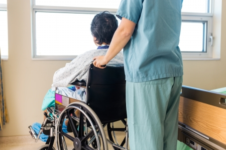 Midsection of nurse holding patients wheelchairs handle by window in hospital photo