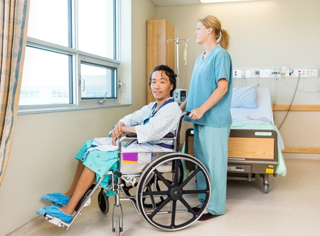 Wheel chair: Full length portrait of male patient sitting on wheel chair with nurse standing behind at window in hospital