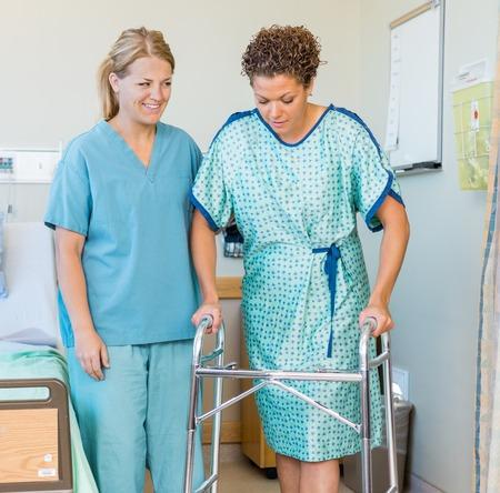 marcheur: Longueur de mi adulte patiente à marcher avec l'aide d'une marchette alors infirmière regardant à l'hôpital