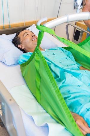 Maturo maschio paziente sdraiato sul imbracatura di sollevamento idraulico sul letto in ospedale