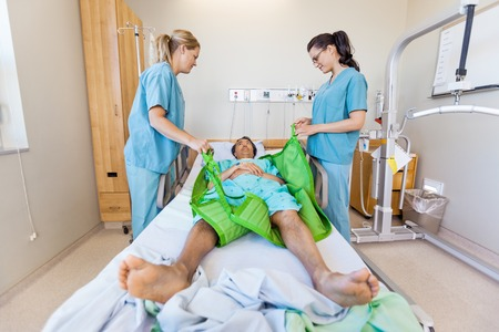 transferring: Nurses preparing male patient before transferring him on hydraulic lift on bed at hospital