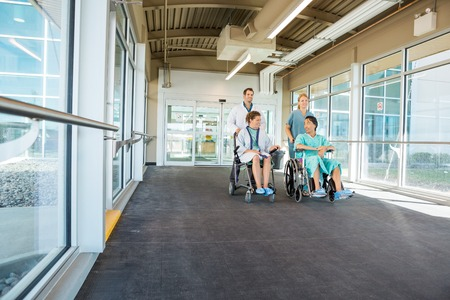 Doctor and nurse pushing patients on wheelchairs at corridor in hospital photo