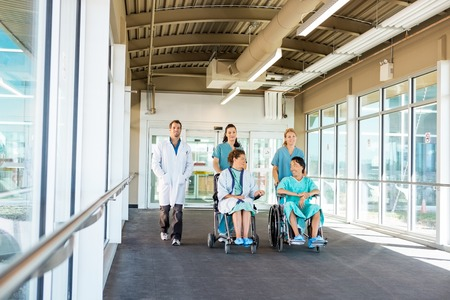 Nurses pushing patients on wheelchairs while walking with doctor at corridor in hospital photo