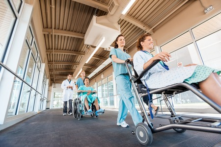 Low angle view of female nurses pushing patients on wheelchairs with doctor walking at corridor in hospital Stock Photo