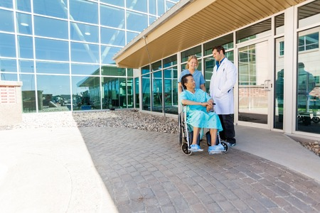 medical building: Full length of nurse and doctor looking at patient on wheelchair at hospital courtyard