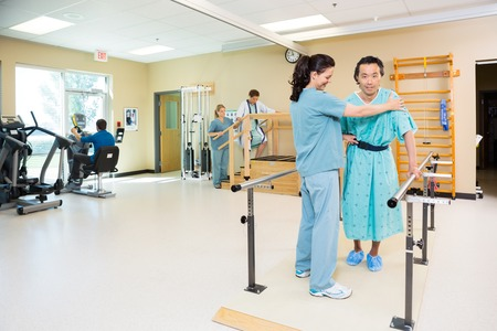 Physical therapists assisting patients in hospital gym Stock Photo