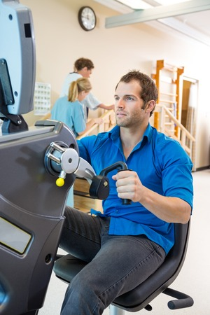 physical fitness: Young man on exercise bike with physical therapist assisting patient in hospital
