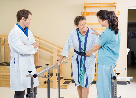 therapist: Female patient being assisted by physical therapists in hospital Stock Photo