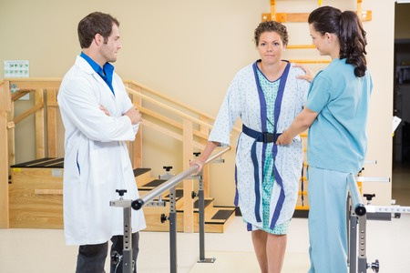 therapy room: Physical therapist with doctor assisting female patient in walking with the support of bars
