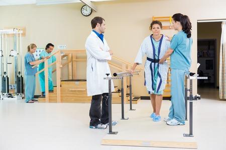Fysiotherapeuten vrouwelijke patiënt bijstaan in het lopen met de steun van leuningen Stockfoto
