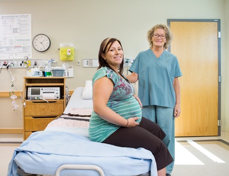 Portrait of happy mature female nurse and pregnant woman in hospital room photo