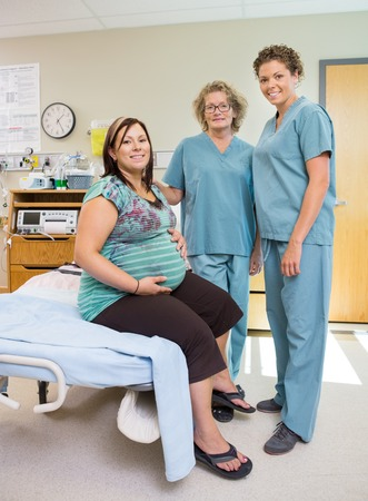 Full length portrait of happy mature female nurses with pregnant woman in hospital room photo