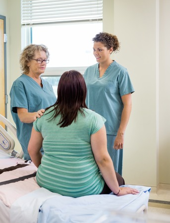 causal clothing: Female nurses and pregnant woman communicating in hospital room